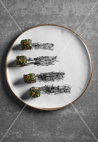 Caviar Sushi Served on a Black Square Platter with Dipping Sauce and Chopsticks