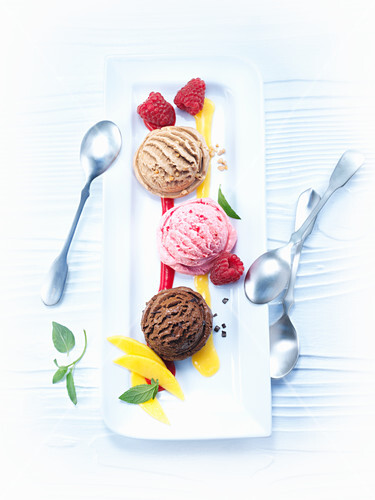 Various ice cream scoops with mango and raspberry sauce
