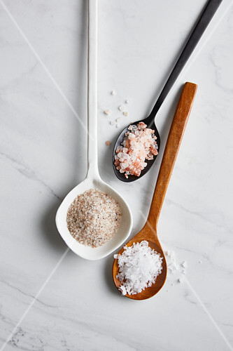 Sea salt, rock salt and Himalayan salt on spoons