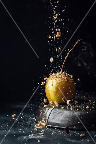 Karamellapfel mit gehackten Nüssen bestreuen