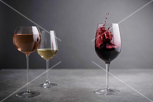 Rotweinglas mit Splash daneben Rosewein- und Weissweinglas
