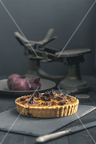 Spelt shortcrust case with butternut squash and red onion filling quiche on a dark background in a mystic style