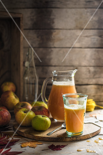 Freshly pressed apple juice in a jug and glass with apples