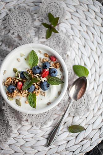 Smoothie bowl with yougurt, blueberries, seed and mint leaves