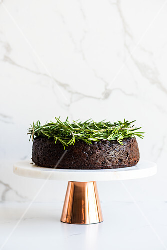 Vegan fruit cake decorated with rosemary sprigs on a cake stand