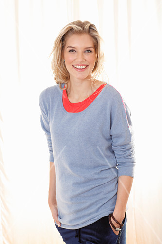 a3c0a1de588 A young blonde woman wearing a blue jumper over a red top – buy ...