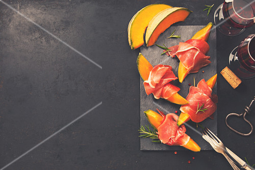 Prosciutto ham with cantaloupe melon, basil leaves and wine over dark grunge background