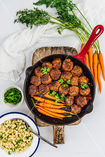 Gluten-Free Honey Garlic Meatballs and roasted baby carrots in a cast iron pan placed on a wooden cutting board