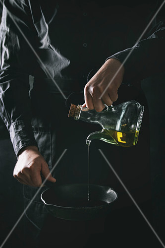 Man chef in black apron pouring olive oil from bottle for cooking pancakes in cast-iron pan
