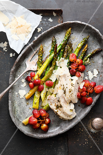 Asparagus with chicken breast and grapes on a baking tray