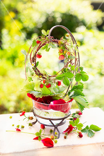 A wreath of wild strawberry stems hung over a glass bowl filled with water and rose petals