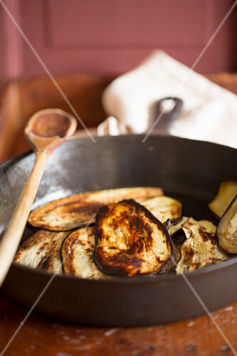 Aubergine slices being fried in oil