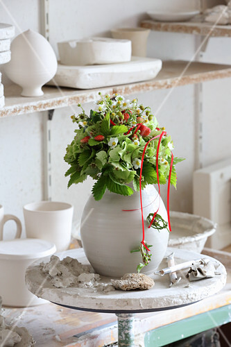 Bouquet of strawberry plants in clay vase