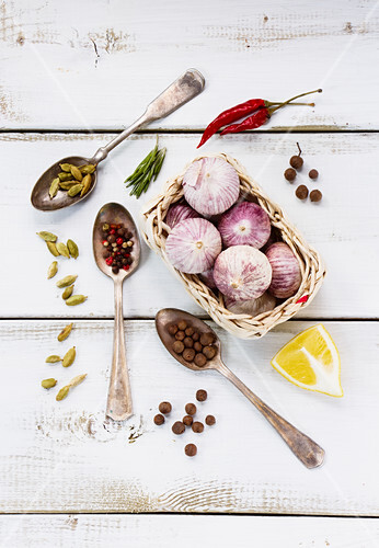 Spices, herbs and garlic on a white wooden surface (seen from above)