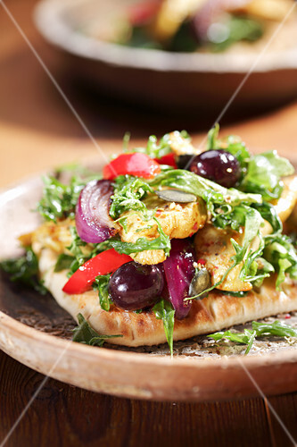 Pitta bread filled with curried chicken, rocket, onions, peppers and olives
