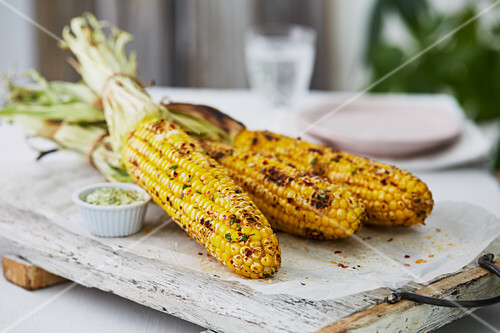 Grilled corn cobs on a wooden board