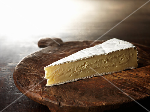 A piece of brie on a wooden plate