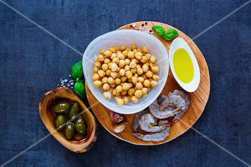 Colorful chickpeas salad ingredients in bowls on round wooden board over dark stone concrete background