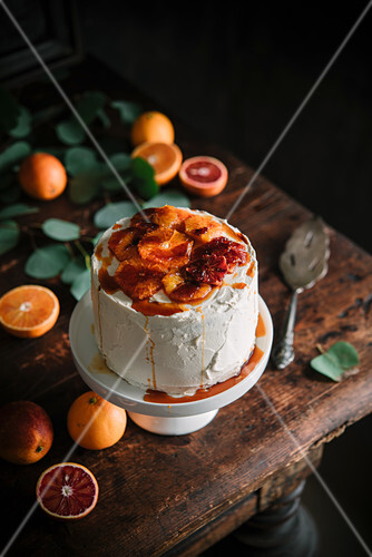 Blood orange cake with caramel sauce on a cake stand
