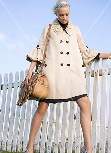 A blonde woman wearing a short, pale coat