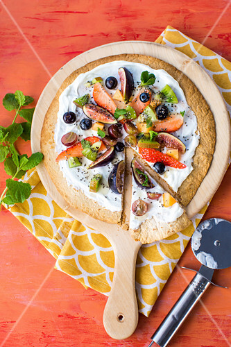 Fruit Pizza made from a toasted Tortilla wrap base, with natural yogurt, fresh fruit toppings, chia seeds and mint to garnish