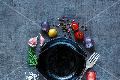 Raw vegetables background with various organic ingredients (potatoes, tomatoes, garlic and spices) over dark grunge table