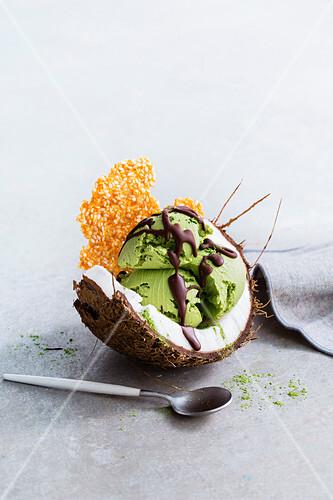 Kokos-Matcha-Eis mit Sesamkrokant in der Kokosnuss