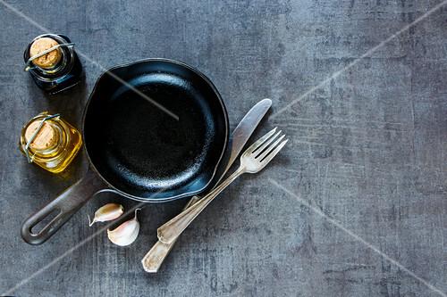 Stillleben mit Bratpfanne, Essig, Öl, Knoblauch und Besteck (Aufsicht)