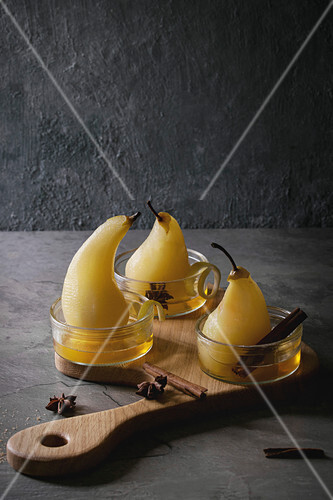 Traditional dessert poached pears in white wine served in glass bowls with syrup and lemon zest on wooden serving board