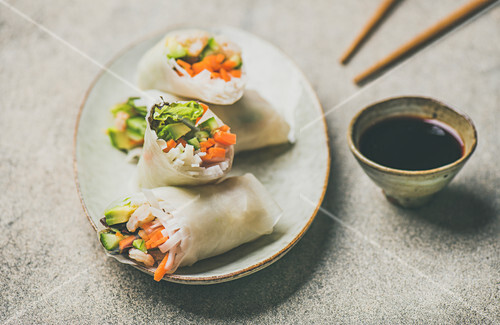 Shrimp and vegetable rice paper spring rolls with sauce and chopsticks on plate over grey background