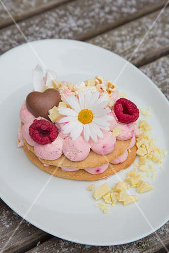 A slice of lavishly decorated flower-shaped cake with raspberry mascarpone cream