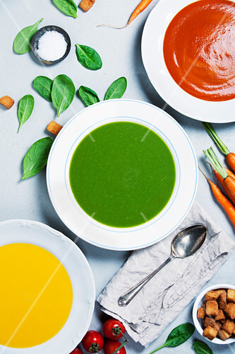 Pumpkin, tomato and spinach soups over grey concrete background