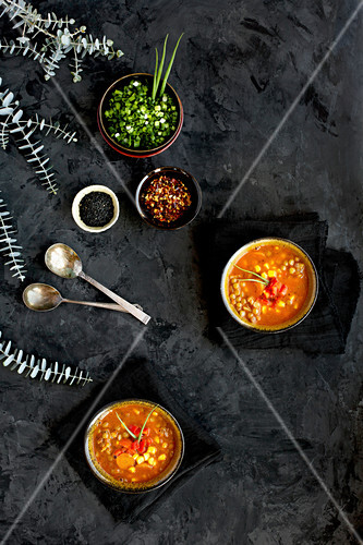 Bowls of Sesame Lentil Soup topped with roasted red peppers and chives