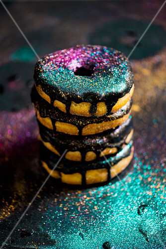 Donuts with a chocolate glaze and glitter, stacked