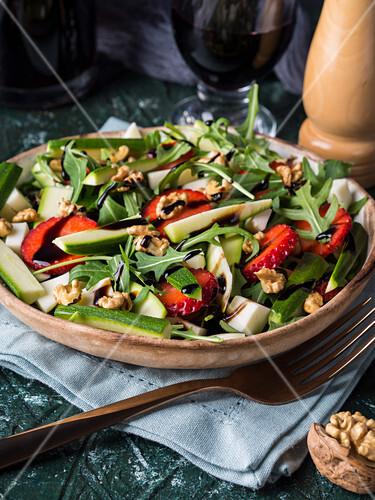 Salad with raw zucchini, strawberries, arugula, diced cheese, walnuts and balsamic glaze