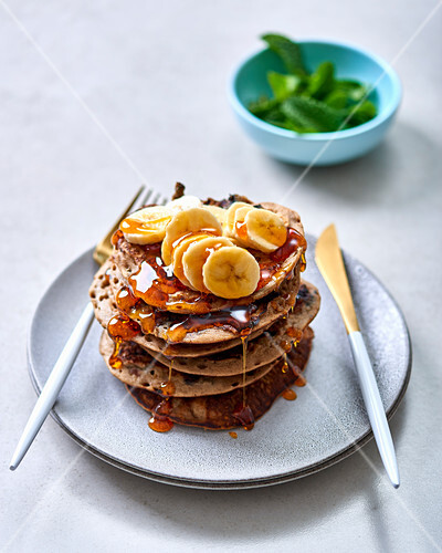 A stack of buckwheat pancakes with blueberries, bananas and syrup