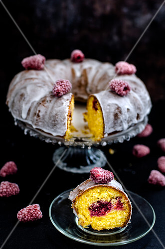 Bundt polenta cake with raspberry on a black surface