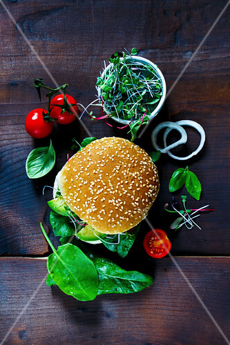 Top view of vegetarian sandwich with avocado, tomatoes, spinach, basil and sprout over old wood dark background