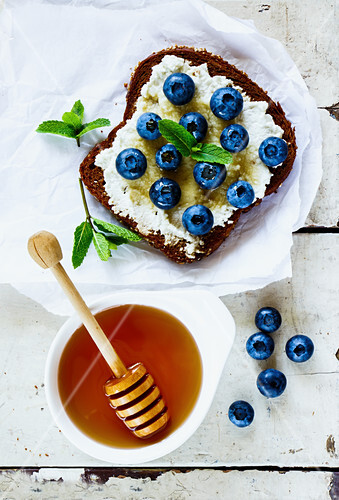 Close up of grunge white wooden table with ricotta, fresh blueberries and honey sandwich on whole grain bread