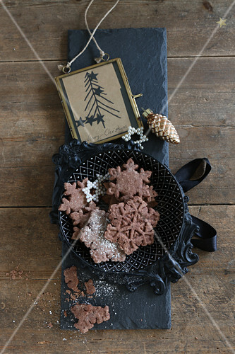 Gluten-free snowflake biscuits with cocoa and icing sugar for Christmas
