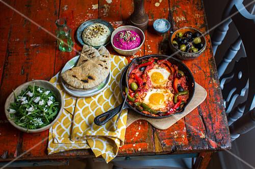 Vegetarisches Shakshuka mit Ei, Rote-Bete-Hummus, Hummus, Oliven, Pitabrot und Rucola mit Feta