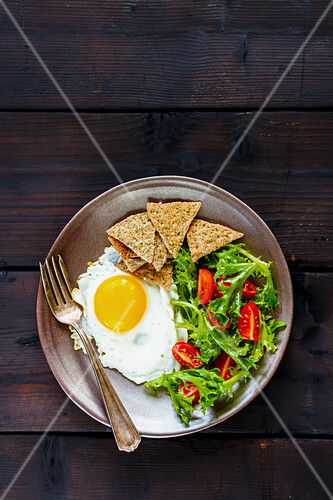 Vegetarian breakfast with a fried egg, salad and crackers (seen from above)