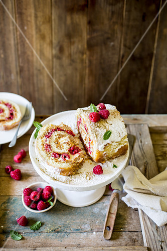 Festive vanilla and raspberry swiss roll with cream cheese filling and gold dust on wooden rustic surface