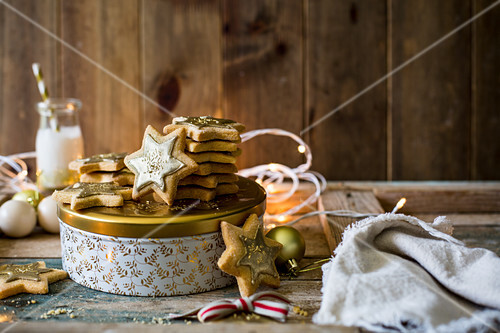 Festive star sugar cookies with golden royal icing and sprinkles with milk on golden and white cookie tin for a gift