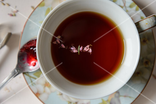 A cup of black tea with herbs, a spoon with red jam
