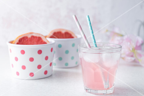 A glass of pink colored grapefruit infused water with pastel colored beverage straws, halved grapefruit in polka dotted bowls