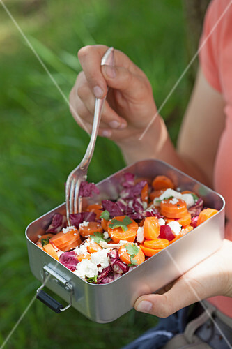 A woman eating a salad with radicchio, carrots and sheep's cheese