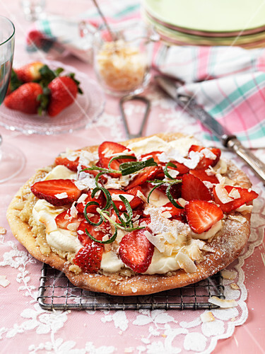 Sweet pizza with almond cream, whipped cream, strawberries and rosemary