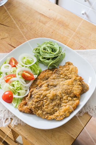 Breaded schnitzel with salad and herb spaghetti