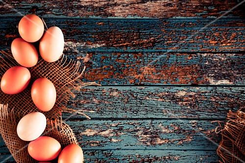 Braue Hühnereier auf Sackleinen und Holzuntergrund (Aufsicht)